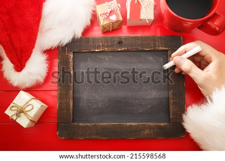 Small blank blackboard with Christmas wishlist on red table - stock photo