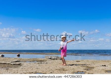 small blond girl wearing pink clothing and cap standing on rocky sea beach with shallow water and pointing away with finger