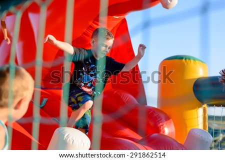 Small blonde boy (6-8 years) wearing t-shirt and shorts concentrating hard on playing outside in red bouncy castle, netting and child visible in foreground - stock photo