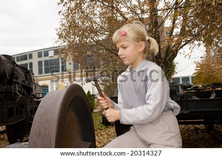 Small blonde girl examines a train wheel with a hammer at an open-air museum.