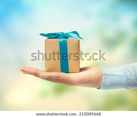 Small blue ribbon gift box on a hand - stock photo