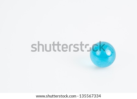 Small blue transparent glass marble on a white background - stock photo