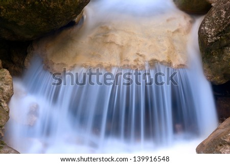 Small blue waterfall on mountain river - stock photo