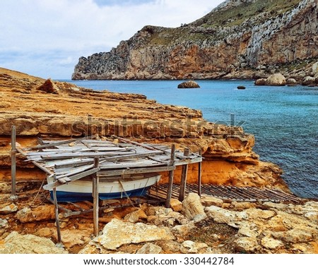 Small boat hidden under a ramshackle wooden shelter, with a wooden ramp leading into the Mediterranean Sea - stock photo