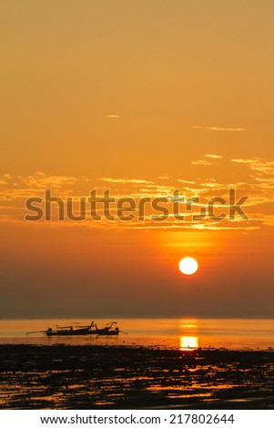 Small boat on a sea coast at the sunset - stock photo
