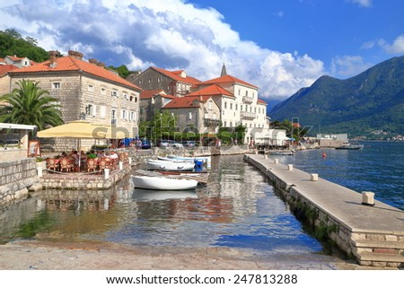 Small boats inside traditional harbor and town on the shores of the Adriatic sea, Perast, Montenegro - stock photo