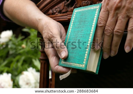 Small book holding by female hands, leaned on retro chair, garden in the blurred background