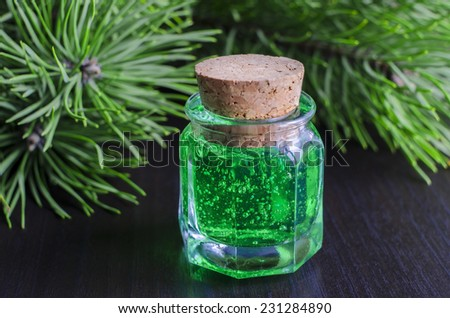 Small bottle of green gel and pine branches - stock photo