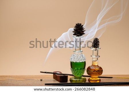 Small bottles of perfume dacorated with smoke from aromatic sticks - stock photo