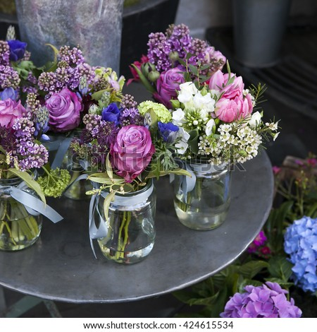 Small bouquets of lilacs, hyacinths, anemones, roses and peonies in small glass jars on an iron table. - stock photo