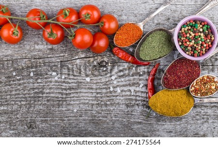 Small bowl and antic metal spoons with different kinds of spices, bunch of cherry tomatoes, sea salt and red hot chili peppers on old wooden board. Selective focus. - stock photo