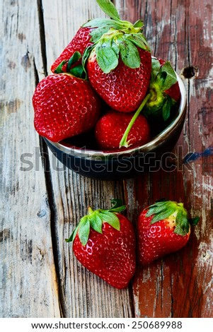 Small bowl filled with juicy fresh ripe red strawberries on an old wooden texture. - stock photo