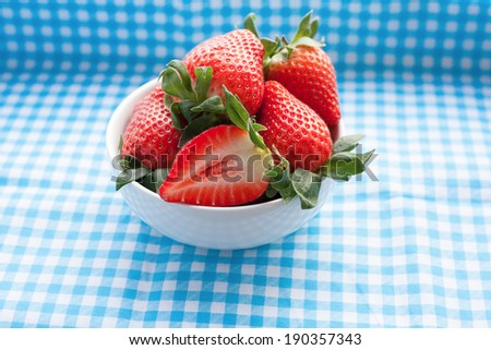 Small bowl filled with succulent juicy fresh ripe red strawberries on table with blue checkered tablecloth