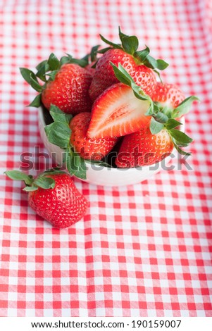 Small bowl filled with succulent juicy fresh ripe red strawberries on table with red checkered tablecloth