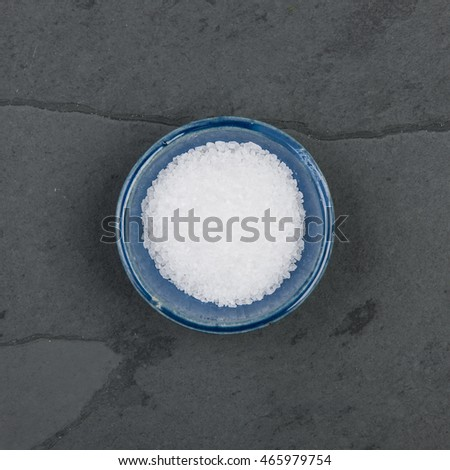 Small bowl of salt, on a grey slate table