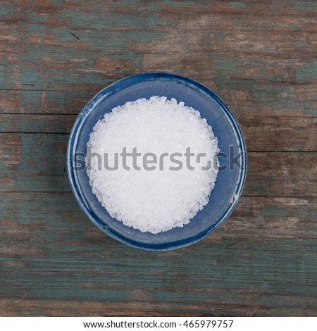Small bowl of salt, on a wooden table