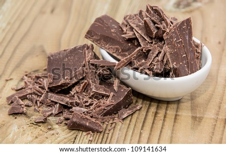 Small bowl with Chocolate on a wooden background