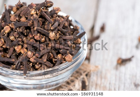 Small bowl with Cloves on vintage wooden background - stock photo