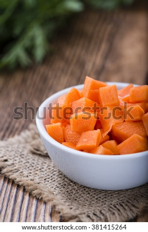 Small bowl with diced carrot (selective focus) on an old wooden table - stock photo