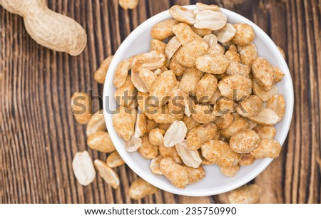 Small bowl with Peanuts (roasted and salted) on wood - stock photo