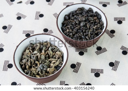 Small bowls of dry green tea leaves on Japanese pattern tablecloth.  - stock photo