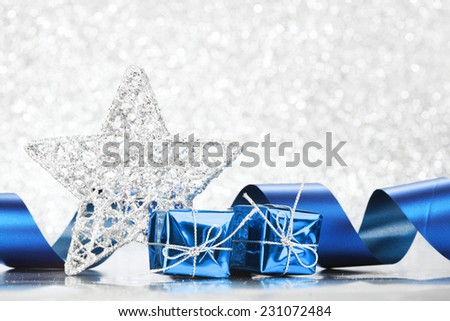 Small boxes with decorative holiday gifts on silver bokeh background - stock photo
