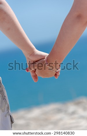 Small boy and girl holding hands on a hill looking down on a sea