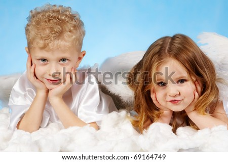 Small boy and girl in angelic costume lying on white cloud
