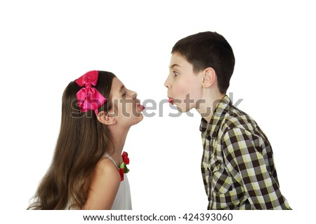 Small boy and girl tease one another show tongues isolated on white background - stock photo