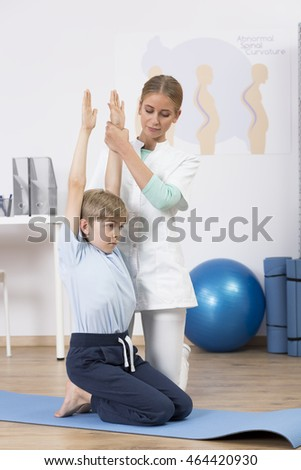 Small boy and young physiotherapist helping him during physical exercises