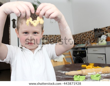 Small boy baking cookies. He holds a piece of dough, which he did. - stock photo