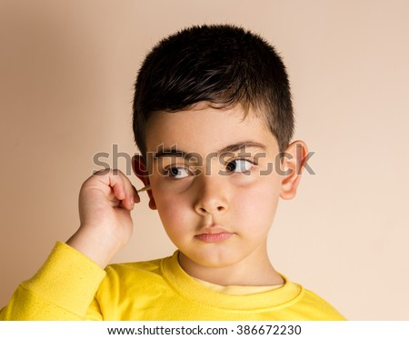 Small boy cleaning his ear - stock photo