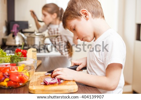 Small boy cooking together with his sister. Cute boy cutting onion for salad in the kitchen. Family cooking background