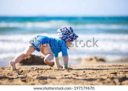 Small boy crawling towards water at the beach - stock photo