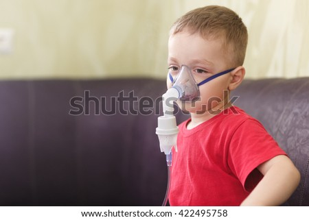 Small boy does therapeutic inhalation using a nebulizer - stock photo
