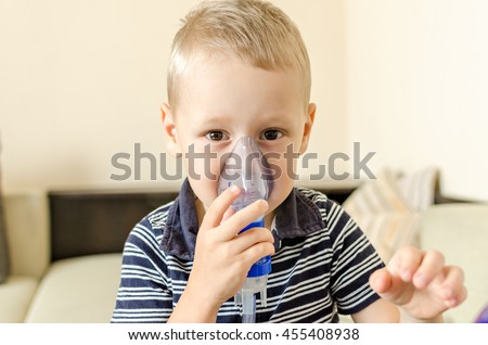 Small boy does therapeutic inhalation using a nebulizer. Child with inhalation mask on face    - stock photo