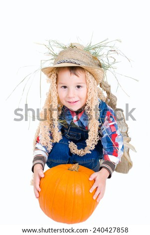 small boy dressed as a scarecrow with a pumpkin - stock photo