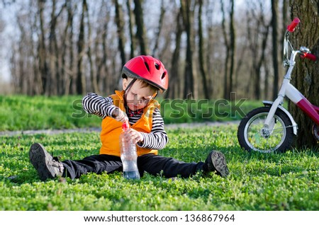 Small boy dressed in a safety helmet and jacket opening a bottle of water while sitting on green grass in a wooded park with his bicycle leaning on a tree nearby - stock photo