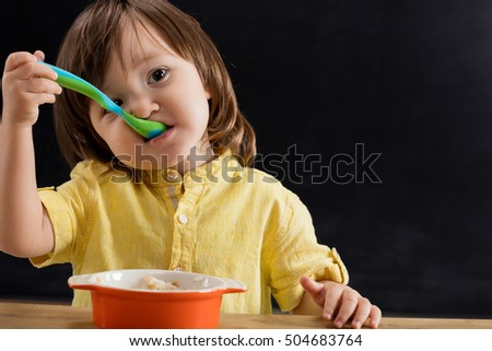 Small boy eating baby food.