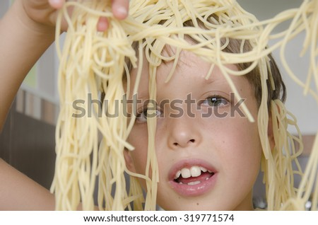 Small boy eating spaghetti with fork and smiles. - stock photo