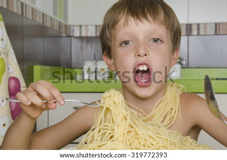 Small boy eating spaghetti with fork and smiles.