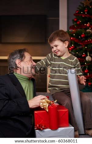 Small boy getting christmas present from happy grandfather, looking each other, smiling. ? - stock photo