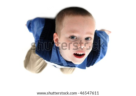 Small boy hangs from the ceiling.  He is truly hanging upside down.  He is wearing khakis and navy blue sweater. - stock photo