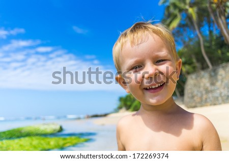 Small boy having fun at the beach - stock photo
