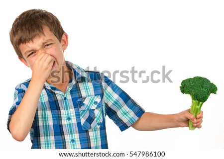 Small Boy Holding a Bunch of Broccoli and has a disgusted look on his face