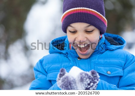 small boy holding snow and smiling. little boy playing outside in park - stock photo