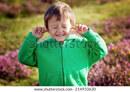 Small boy holds his hands over ears not to hear, making sweet funny face - stock photo