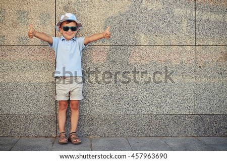 Small boy in casual summer clothes and sunglasses is standing near the wall in the street and giving thumbs up - stock photo