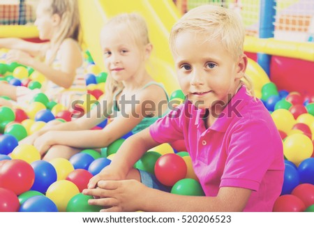 Small boy in elementary school age sitting and playing with multicolored plastic balls