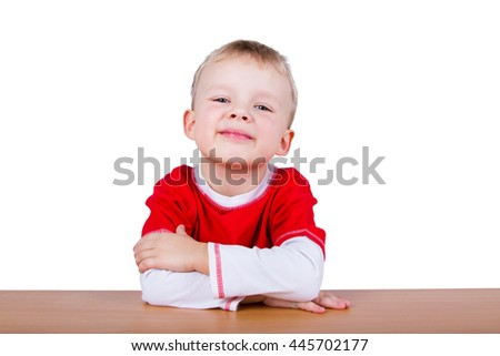 Small boy in red T-shirt, sitting at the table. Isolated on a white background
